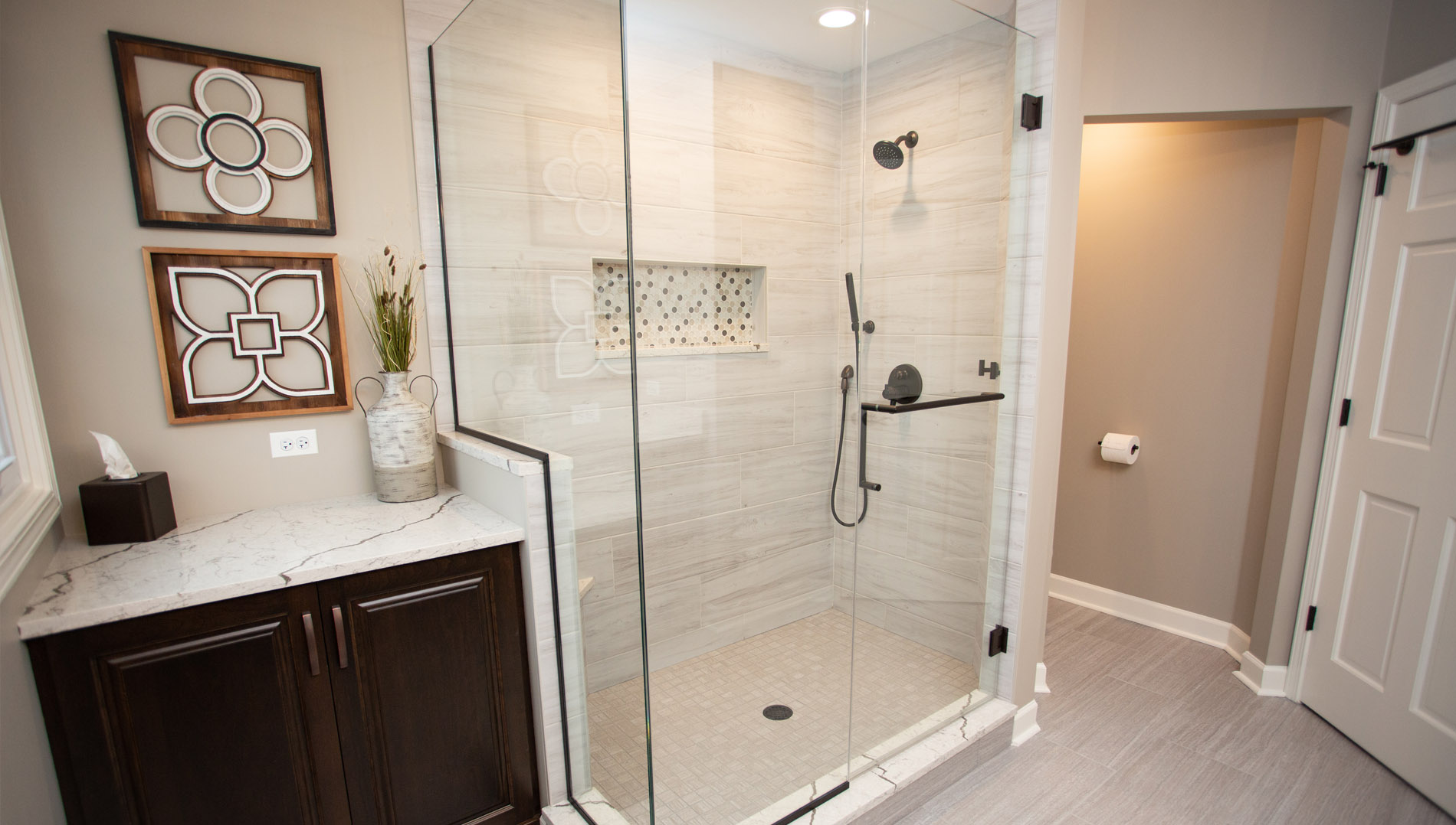 Large glassed in shower with storage cabinet and private water closet.