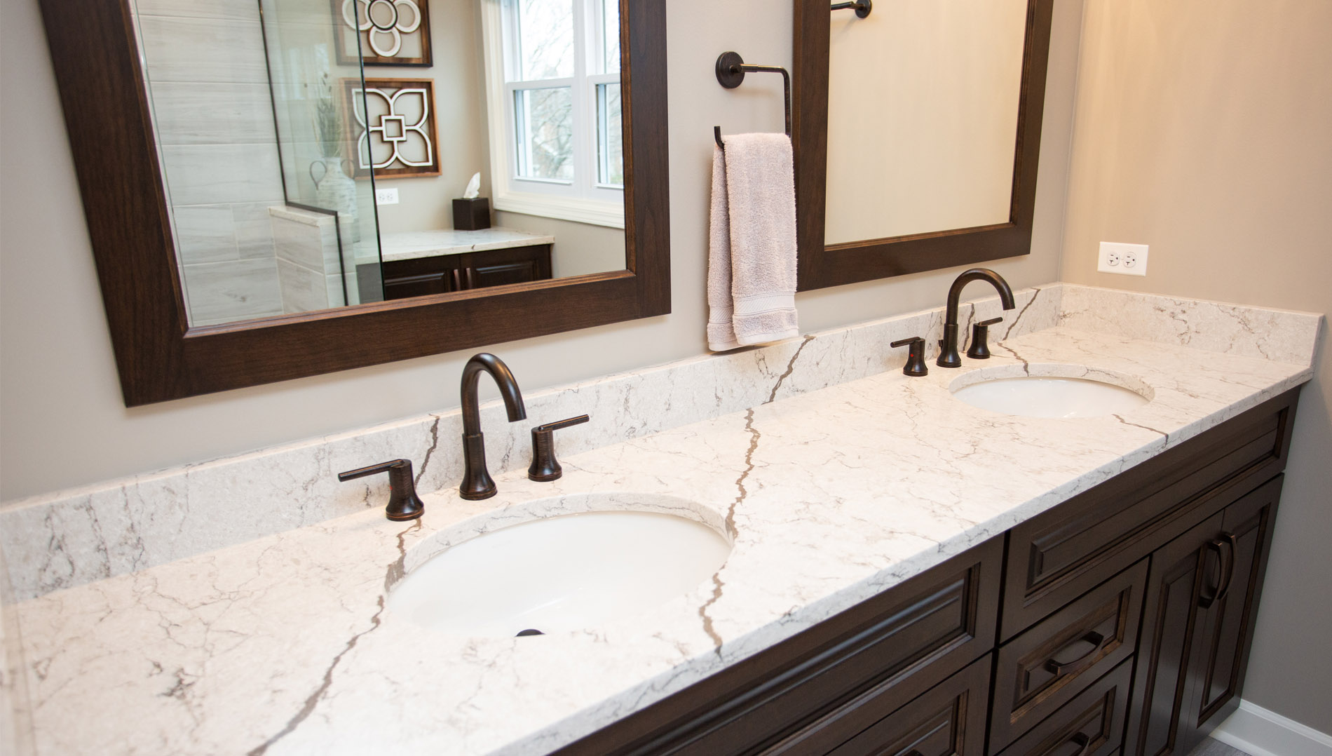 Double vanity with undermount oval sinks and counters topped with Vicostone Diamante quarts