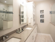 Elongated white double vanity with tower cabinet linen storage.