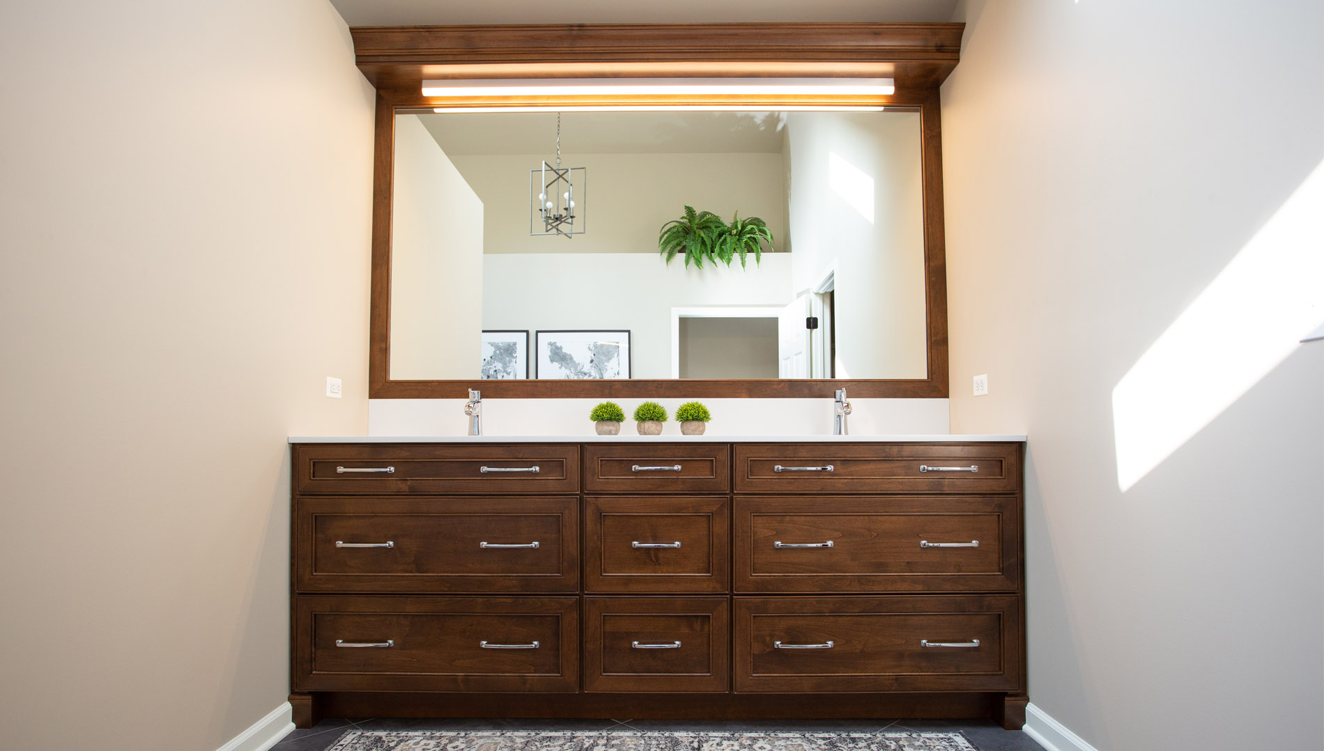 Large stained alder wood double vanity with framed mirror and light bar.