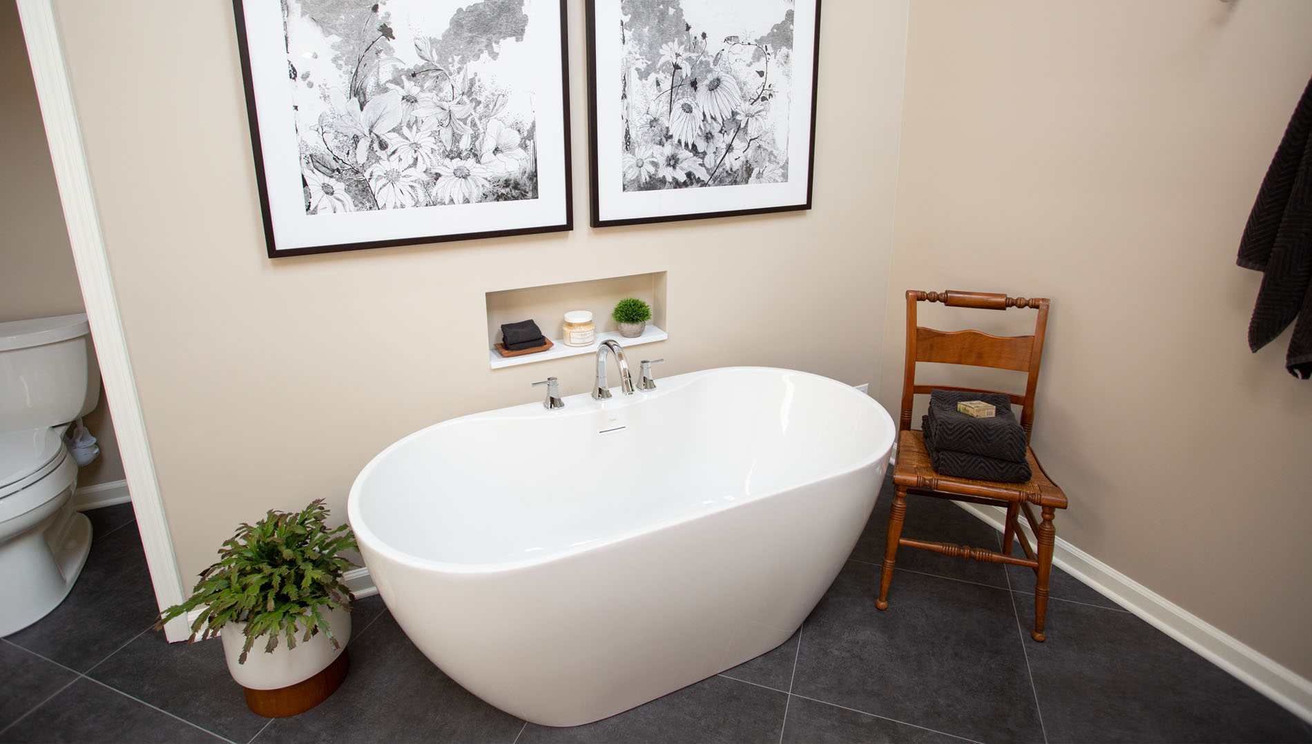 Stand alone white oval bathtub with small niche in wall parallel to the fixtures of tub.