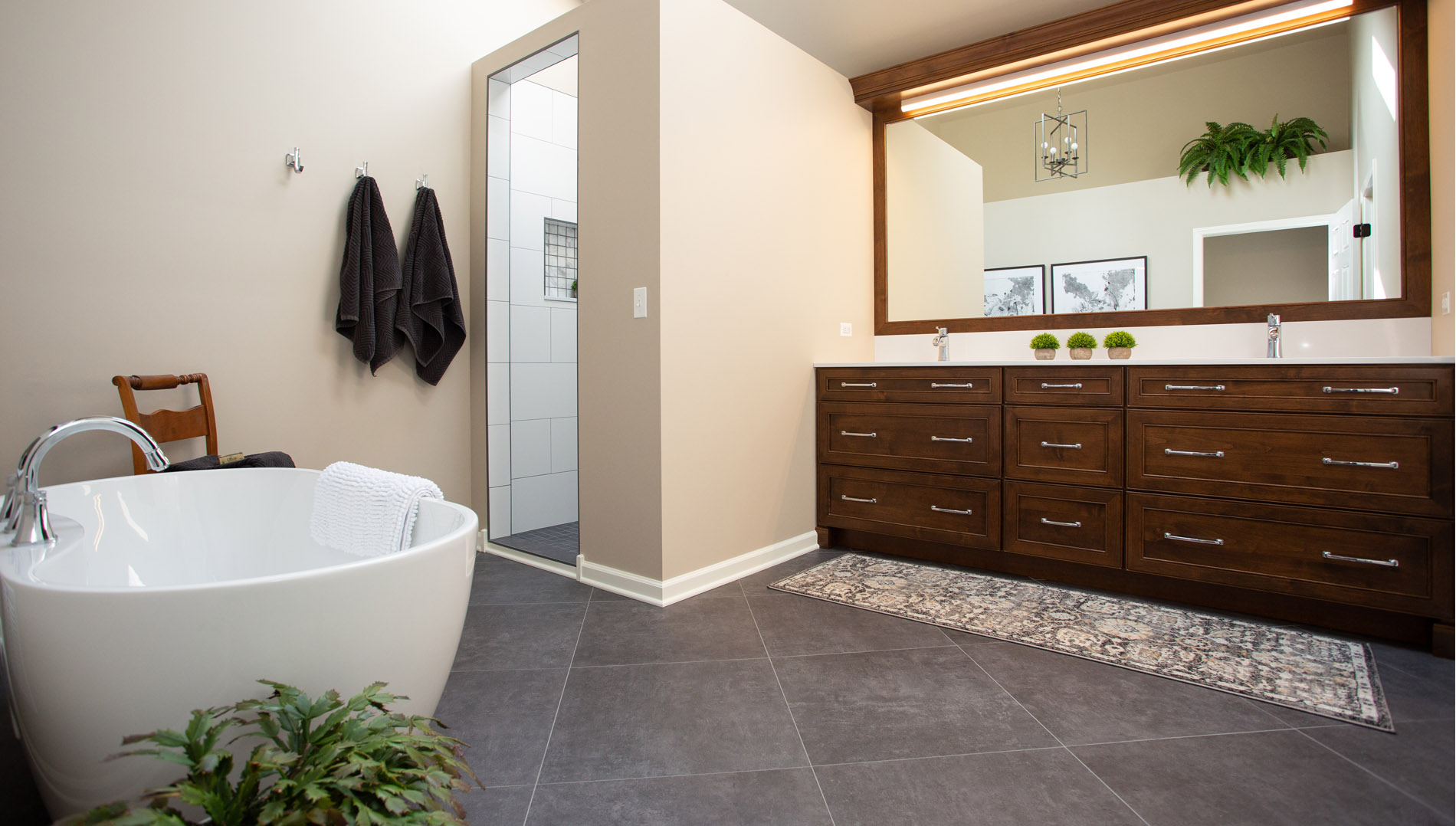 Master bathroom with grey floor tile, walk in shower, standalone tub and double vanity.