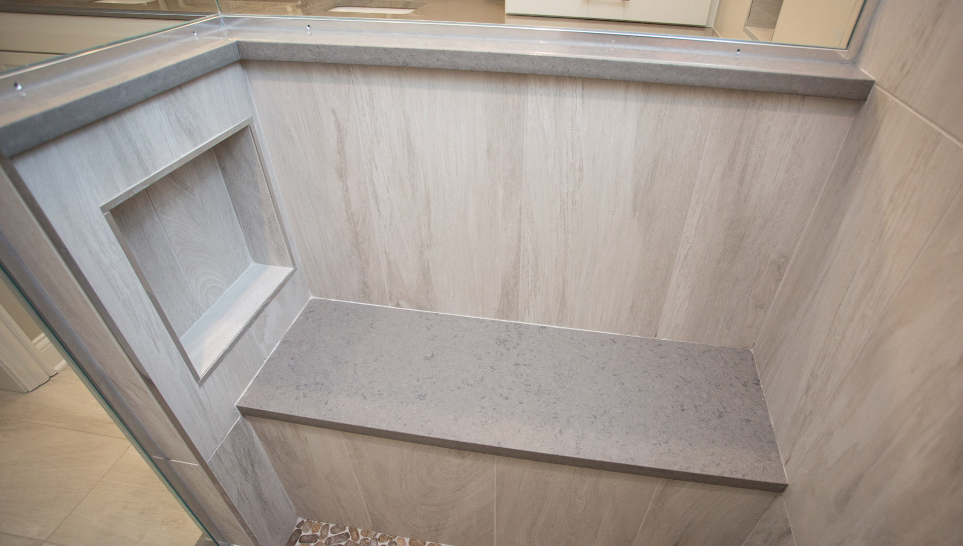Bench seat and toiletry niche inside shower.